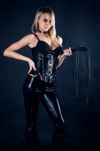 BDSM Mistress with whip in her dungeon