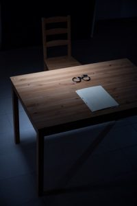 Desk and chair for kinky questioning of suspect.