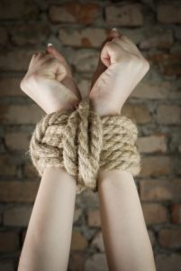 Hands tied with rope using special bondage knots.