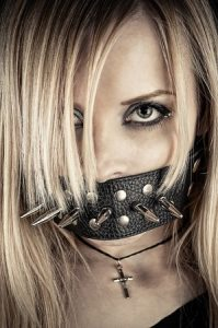 Submissive woman gagged with a leather strap.
